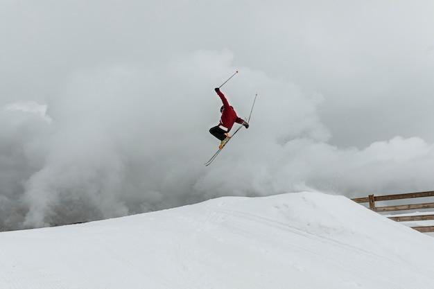 Lang geschoten skiër die over heuvel springt
