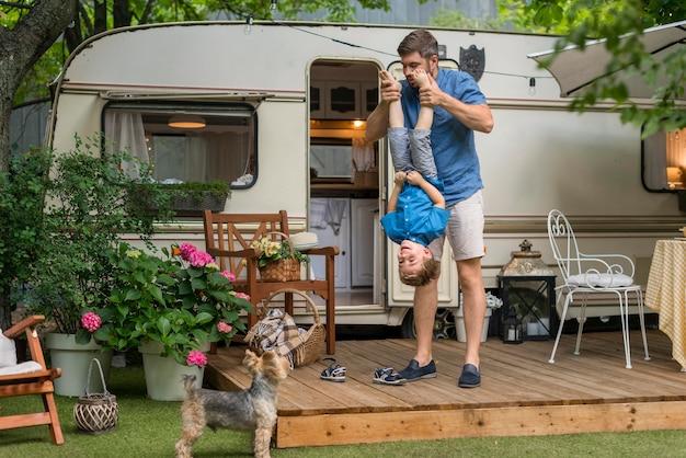 Lang geschoten vader speelt met zijn zoon naast een caravan