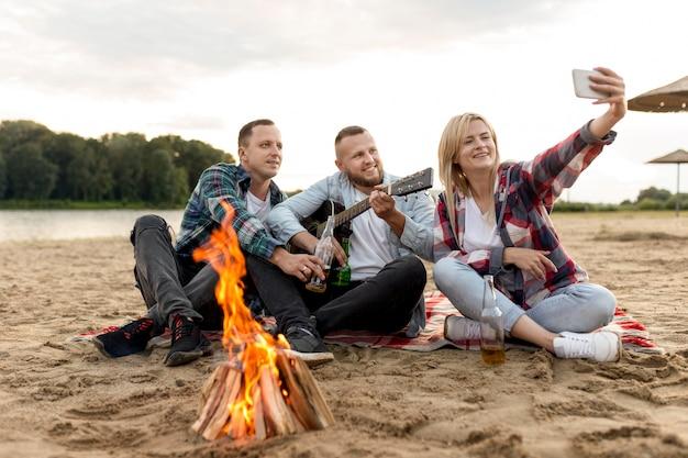 Lang geschoten vrienden die een selfie nemen terwijl ze op het zand zitten