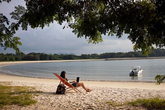 Lang geschoten vrouw die aan laptop bij strand werkt