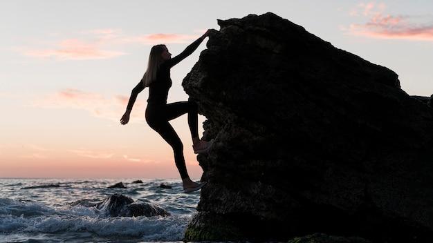 Lang geschoten vrouw die een rots naast de oceaan beklimt