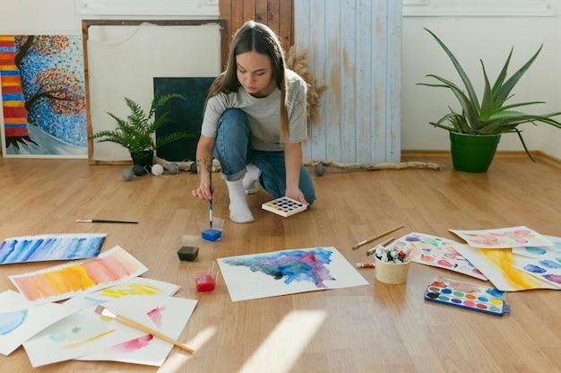 Lang geschoten vrouw die op de vloer schildert