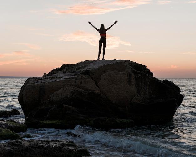 Lang geschoten vrouw staande op een grote rots in de oceaan