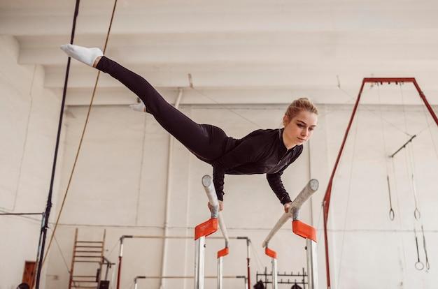 Lang geschoten vrouw training voor gymnastiekkampioenschap
