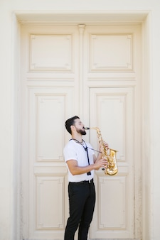 Lang geschoten zijdelings musicus die de saxofoon speelt