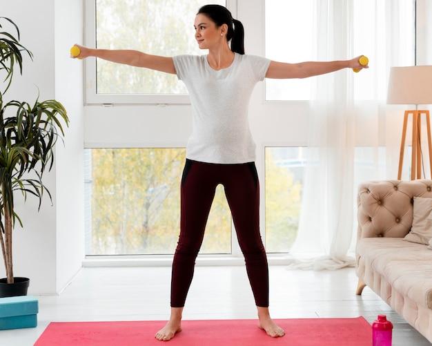 Lang geschoten zwangere vrouw die met gewichten traint