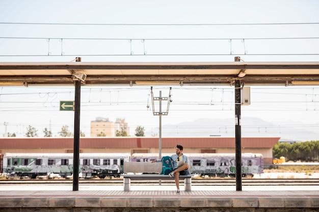 Lang geschotene reiziger die op trein wacht