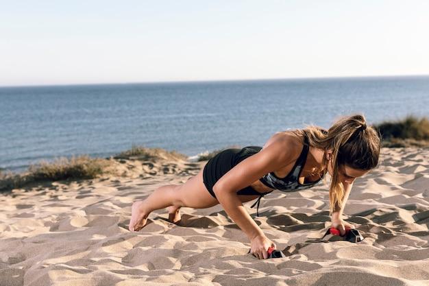 Lang geschotene vrouw die duw ups op het strand doet