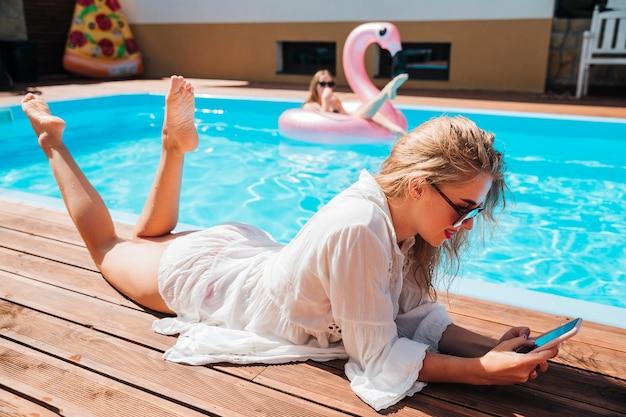Lang geschotene vrouw die haar telefoon controleert bij de pool