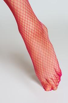 Lang gespierd vrouwelijk been in sexy roze netkousen. vooraanzicht close-up.