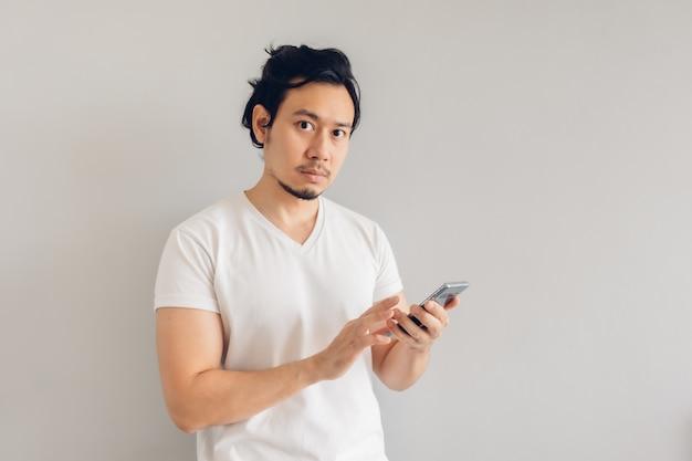 Lang haar man in wit casual t-shirt gebruikt smartphone.