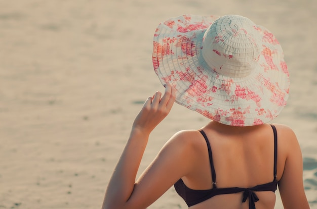 Lang kaukasisch slank meisje houdt een hand over de rand van de dop op het strand, zit op gouden zand. recreatie en verwennerij aan de kust (oceaan, rivier, meer) in de zomer en op zonnige dagen.