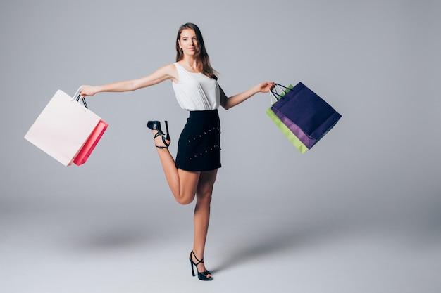 Lang meisje in schoenen met hoge hakken houdt been omhoog en verschillende boodschappentassen op wit wordt geïsoleerd