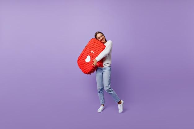 Lang portret van een verfijnd meisje dat geobsedeerd is door sociale netwerken. goed geklede vrouwelijke blogger die zich op paars bevindt