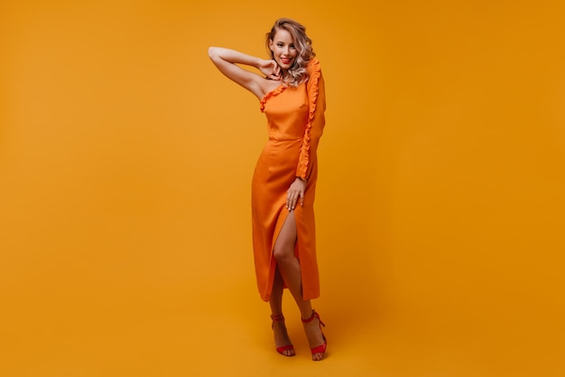 Lang portret van geïnspireerde welgevormde vrouw in oranje jurk