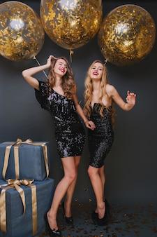 Lang portret van prachtige dames die dansen naast fonkelende ballonnen en lachen. indoor portret van slank blond meisje plezier op haar verjaardagsfeestje met beste vriend.