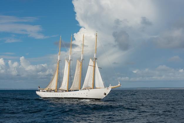 Lang schip met zeilen op zee