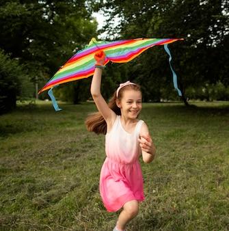 Lang schot van gelukkig meisje dat pret met een vlieger heeft