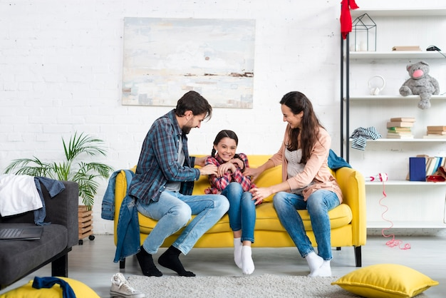 Lang schot van gelukkige familie in woonkamer