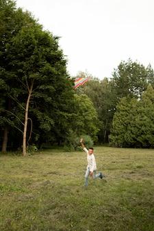 Lang schot van gelukkige jongen die pret met een vlieger heeft