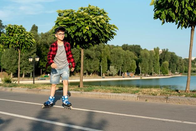 Lang schot van jongen met blauwe gealigneerde schaatsen