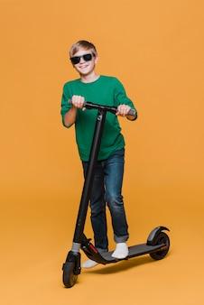 Lang schot van jongen met zonnebril op autoped