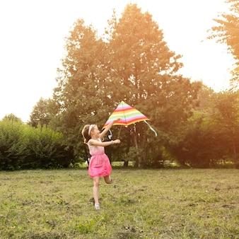 Lang schot van mooi gelukkig meisje met vlieger