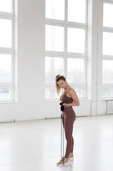 Lang schot van mooie vrouw die gymnastiek doet