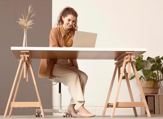Lang schot van persoon die op laptop zit en werkt