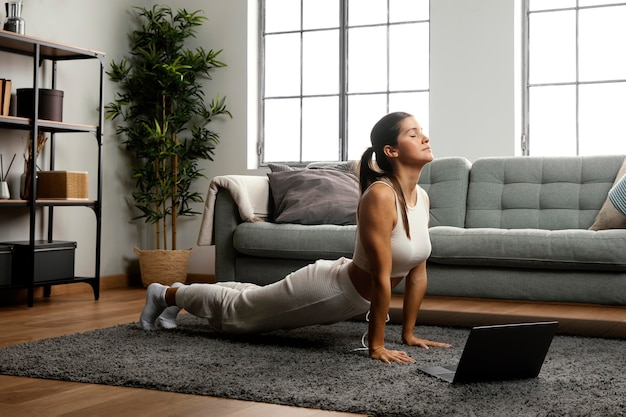 Lang schot van vrouw die yoga beoefent