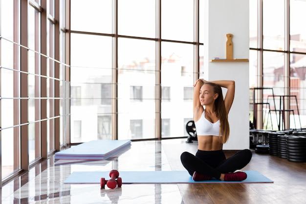Lang schot van vrouw het uitrekken zich in gymnastiek