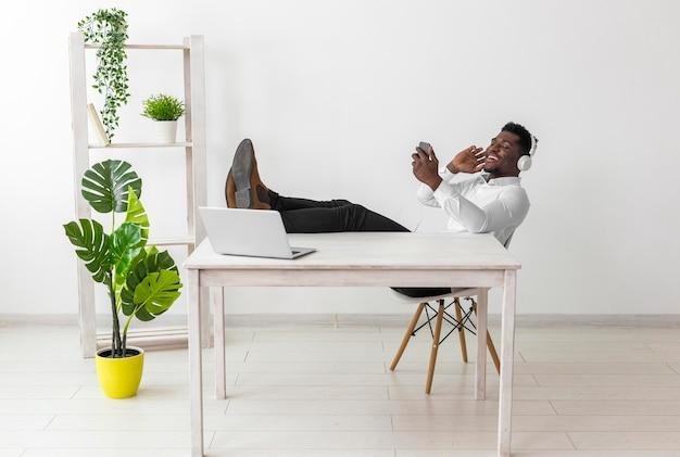 Lang shot van de man die aan het bureau zit en naar muziek luistert