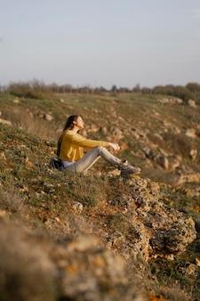 Lang shot van een jonge vrouw die geniet van de natuur om haar heen