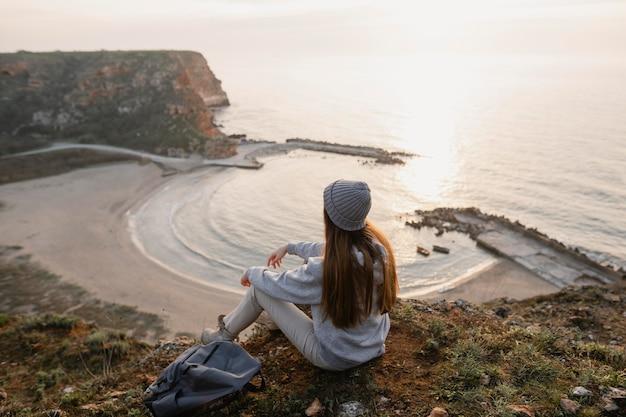 Lang shot van een jonge vrouw die geniet van de rust om haar heen