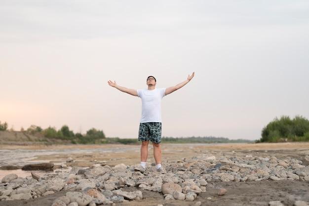 Lang shot van een man die zijn armen in de lucht houdt