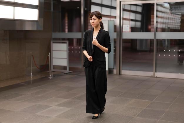 Lang shot van een vrouw voor een gebouw