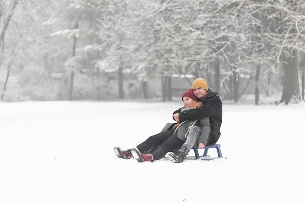Lang shot van paar knuffelen en zittend op de slee