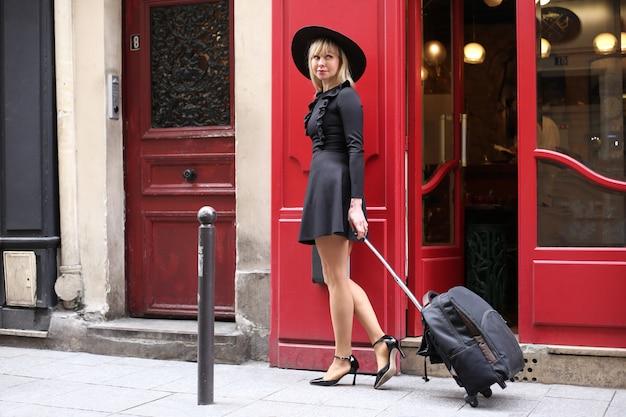 Langbenige blonde in een korte zwarte jurk met een hoed en een koffer loopt over straat in parijs