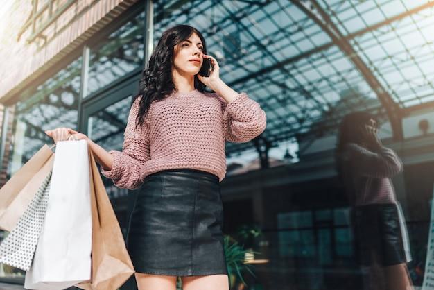 Langbenige brunette vrouw in lederen korte rok staan voor etalage, een bos van papieren zakken in de hand houden en praten op mobiele telefoon