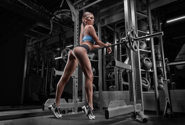 Langbenige meisje poseren in de sportschool. ze leunde op de halter. achteraanzicht.