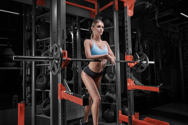 Langbenige meisje poseren in de sportschool. ze leunde op de halter.