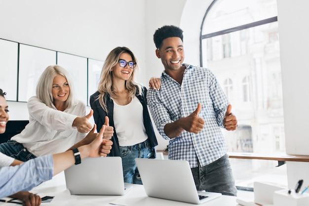 Lange afrikaanse manager met grote glimlach die duimen omhoog houdt en weg kijkt. charmante meisjes werken als managers poseren in kantoor naast tafel met laptops erop en lachen.