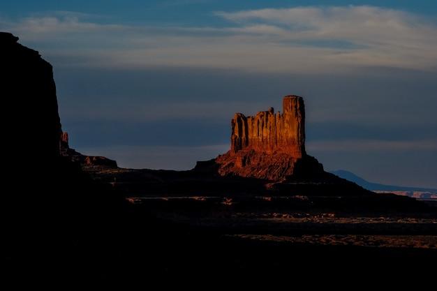 Lange afstand die van grote woestijnrots is ontsproten op een heuvel met bewolkte hemel op de achtergrond
