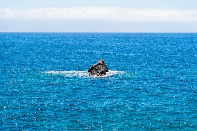 Lange afstand eenzame rots in de kristalheldere zee