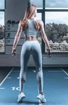 Lange atletische vrouw glimlacht en poseert in de sportschool met een metalen halter. fitness en bodybuilding concept. gemengde media