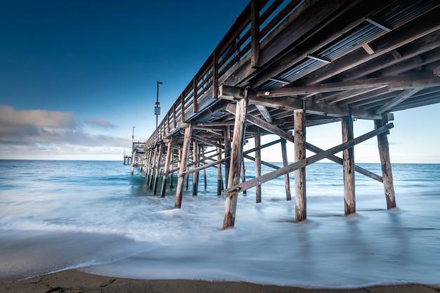 Lange belichtingstijd die van een pier op het strand in californië is ontsproten