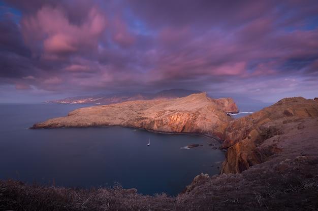 Lange blootstelling landschap bij zonsopgang van een rotsachtige klif roze wazig snelbewegende wolken en lichten van een grote stad op de achtergrond