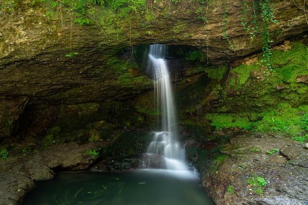 Lange blootstelling murgul deliklikaya waterval over bruine en groene rotsen.