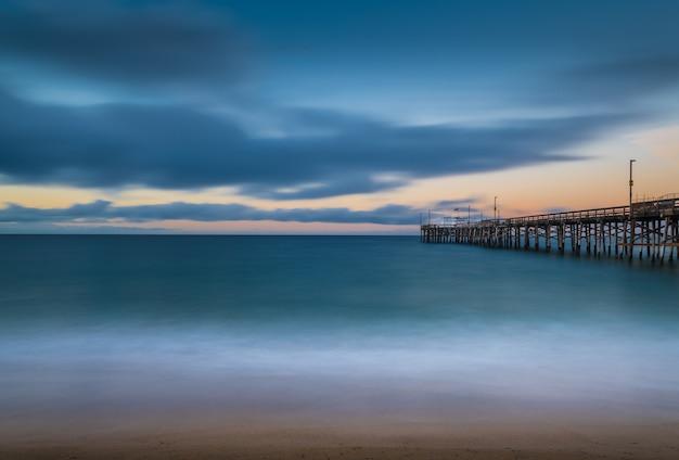 Lange blootstelling van een houten pier in de zee in californië in de avond