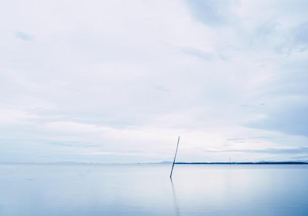 Lange blootstelling van regenachtige wolken boven een kalme zee aan de horizon. abstract zeegezicht bij don hoi lot. samut songkhram thailand